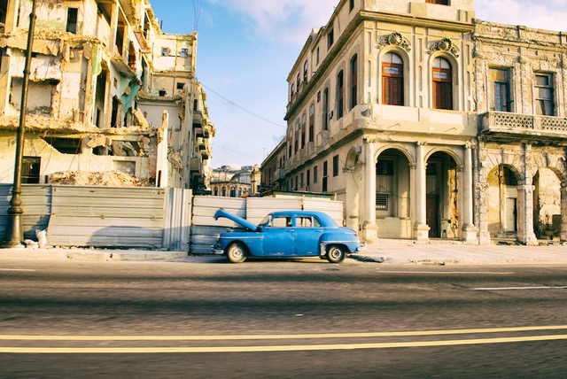 Blue car with its bonnet up on a street in Havana