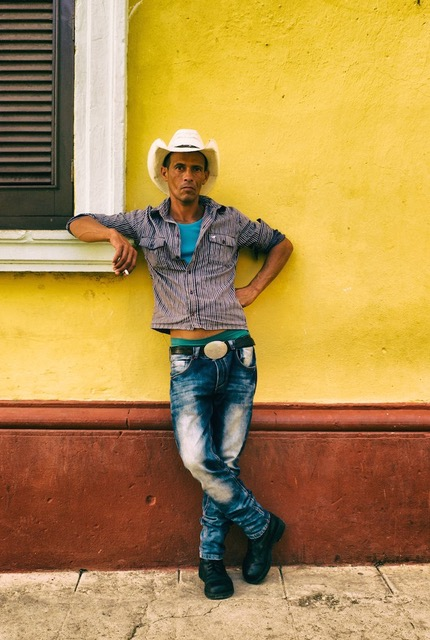 Cowboy with faded jeans leaning on a window ledge