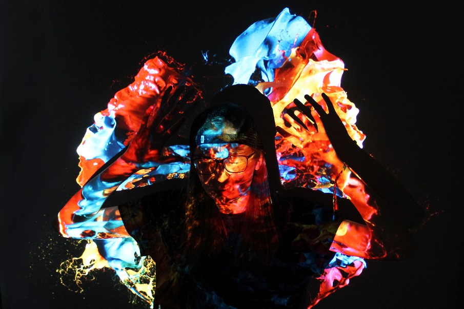 A portrait of a young person standing, arms aloft with an explosion of colour projected onto them.