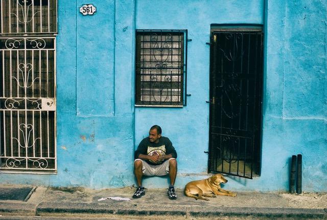 Man and dog sitting against crumbling blue wall, Havan