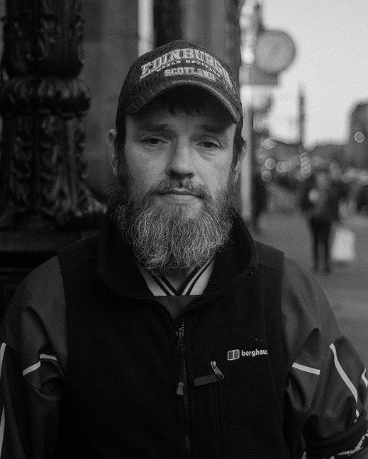 Bearded man in cap photographed in black & white on a busy street